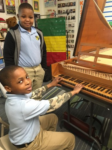 Two young students get up-close with the harpsichord.