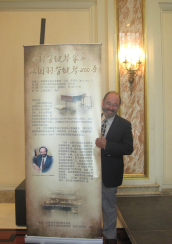 Mark Kroll stands before a poster for his recital in Shanghai.