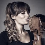 A woman kissing a violin